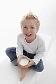 A little boy holding a glass of milk