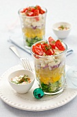 Layered vegetable salad in glasses, yoghurt dressing