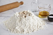 Baking ingredients (flour, yeast, salt, water, oil) and rolling pin