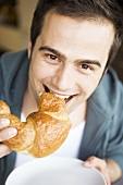 Young man biting into a croissant