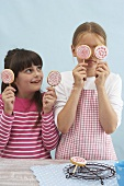 Two girls holding biscuit lollies