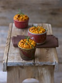 Pumpkin & cheese soufflé in three moulds on a wooden bench