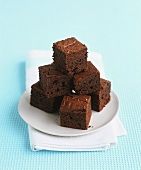 A stack of chocolate brownies on a plate