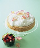 Sponge cake with whipped cream, rose petals and fruit salad