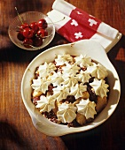 Cherry and apple pudding with meringue rosettes