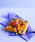 A piece of apricot tart with pistachios