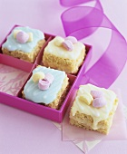 Small cakes with coloured icing in and beside gift box