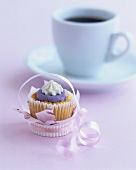 Muffin with coloured icing, cup of coffee