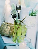 Summery table laid with cutlery and serviettes in a glass