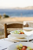 Salad and white wine on laid table by the sea