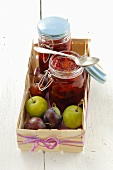Plum jam and fresh plums in a wooden basket
