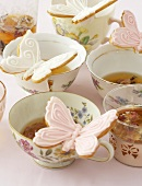 Teatime: tea cups with butterfly biscuits