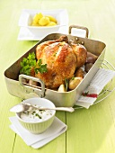 Roast chicken with shallots in a roasting tin