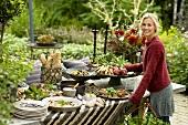 A blonde woman standing by an autumnal buffet