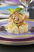 Prawns baked in spring roll dough on a potato and cucumber salad