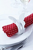 A polka dot naplkin with a butterfly napkin ring
