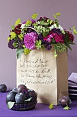 A bouquet of dahlias and stonecrops in a paper bag with plums in front