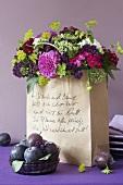 Blumenstrauss mit Balldahlien und Fetter Henner in einer Papiertüte, davor Pflaumen
