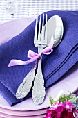 A spoon and a fork on purple napkin