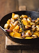 Pumpkin with chestnuts and onions in frying pan