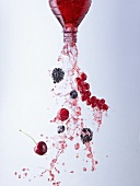 Wild berry juice and berries pouring out of bottle