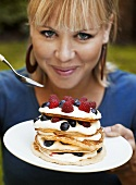 Woman eating pancakes with cream and berries