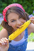 Young woman eating grilled corn on the cob