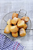 Doughnuts with icing sugar in wire basket