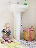 Baby sitting on rug in bathroom