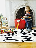 Toddler with toys on rug in front of fireplace