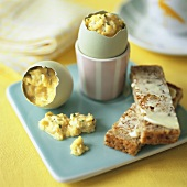 Scrambled egg in eggshell with buttered toast soldiers