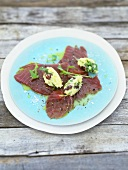 Marinated tuna with crushed potatoes, olives and rocket