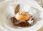 A place setting decorated with a tiny Easter nest