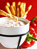 Mozzarella fondue with cheese sticks and peppers