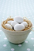 White eggs in a clay pot with straw (Easter)
