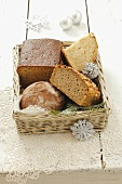 Various types of bread in a bread basket with Christmas decorations