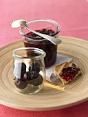 Cherry and coconut jam in jar and on toast