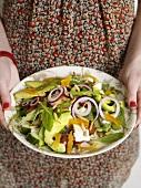 Frau hält Salatteller mit Ziegenkäse und Trockenfrüchten