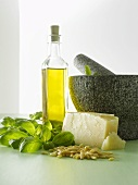 Ingredients for pesto beside mortar and pestle