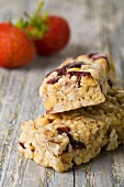 Muesli bars with red fruit on wooden background