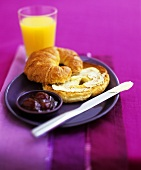 Croissant with butter and jam and a glass of orange juice