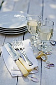 Glasses of white wine, cutlery and plates on wooden table