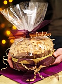 Hands holding gift-wrapped panettone