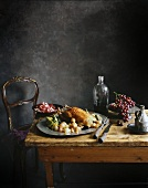 Duck with vegetables and grapes on an old wooden table