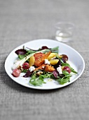 Fried beetroot, radishes and carrots with sheep's cheese on a bed of rocket
