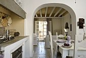 An open-plan dining room with a kitchen and view through an archway into a living room with a wood beamed ceiling