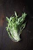 Fresh turnip greens on a wooden background