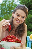 Young woman with freshly picked red currants