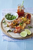 Skewers with ham cubes, pineapples and sweet chili sauce