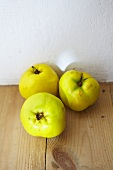 Three quinces on a wooden surface